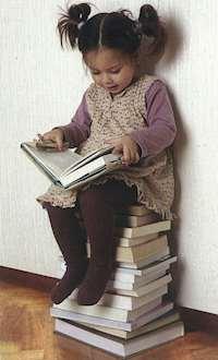 Flicka sitter på en boktrave och läser