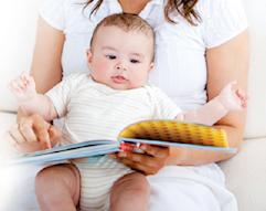 Kvinna som läser för bäbis ur en bok.