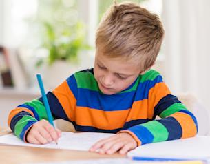 Pojke som skriver på ett papper.