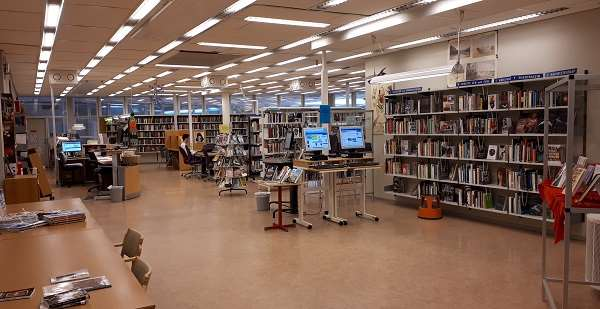 Interiör från Tannbergsskolans bibliotek, där man ser bibliotekets lånedisk, sökdatorer och massa bokhyllor.