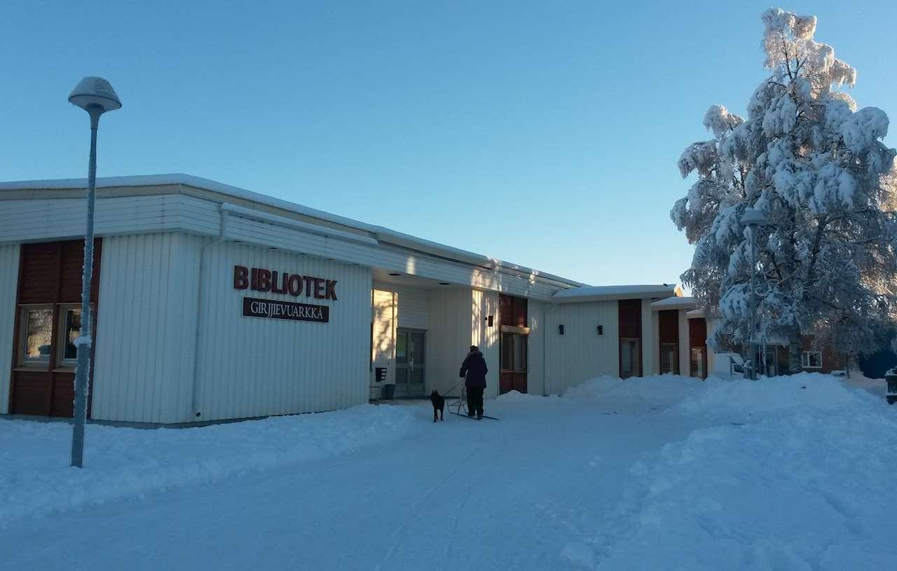 Bild på Sorsele biblioteks fasad en vacker vinterdag. På bilden syns även en kvinna på en spark med en hund
