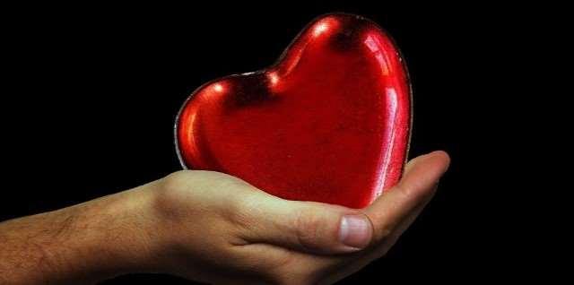 En hand som håller i ett rött hjärta