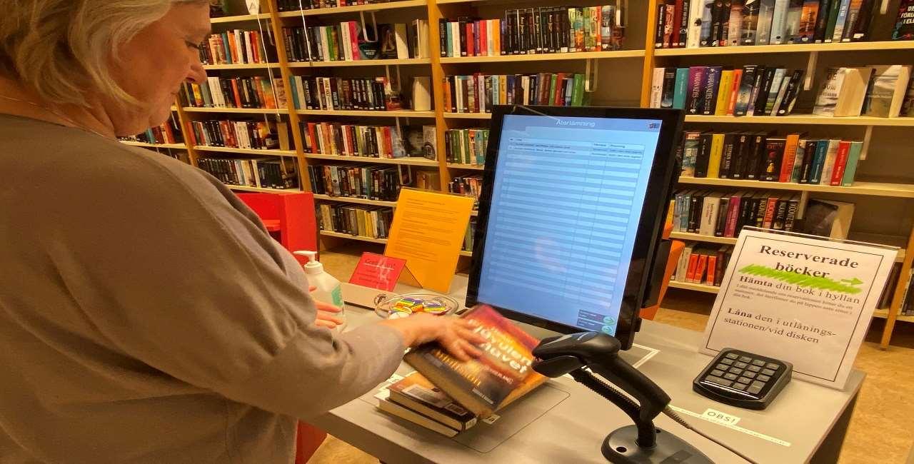 Användare lånar böcker vid utlåningsstation på Åsele bibliotek